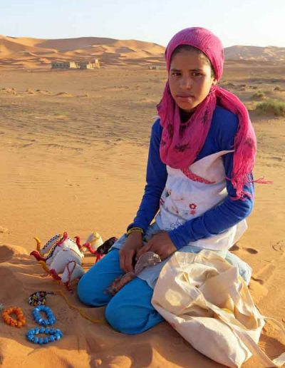 Girl in Sahara with homemade crafts
