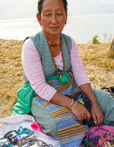Tibetan lady selling hand made jewellery beside Pokhara Lake Nepal
