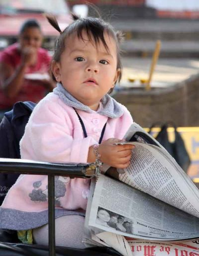 Young girl reading newspaper Michoacan Mexico
