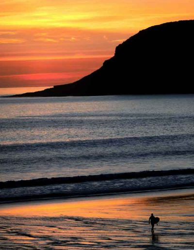 Surfer at sunset Caswell Bay