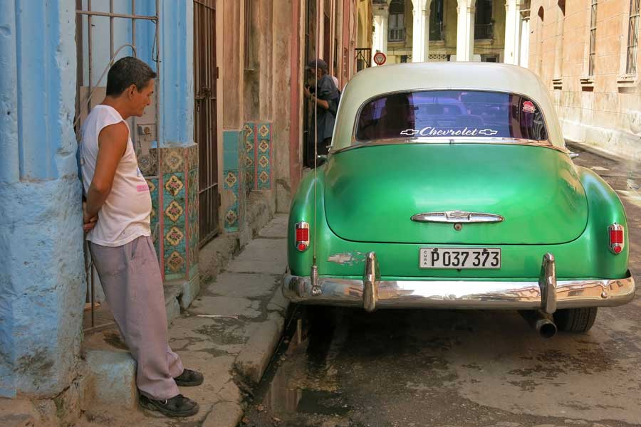 A man looks at  a classic parked on a street Havana Cuba