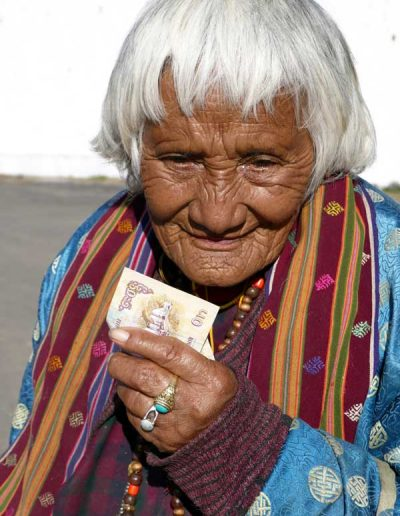 Old lady collecting alms at temple Bhutan