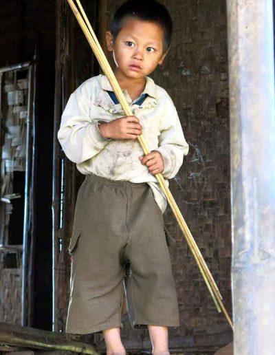 Small boy peering out of his village hut Myanmar